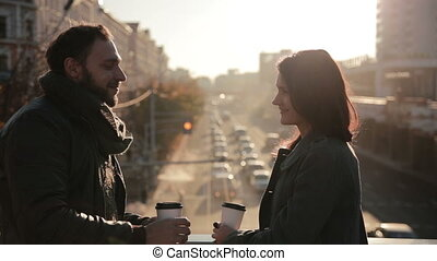 young couple tenderly embracing on a city bridge