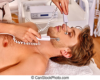 Man receiving electric facial peeling hydradermie massage -...