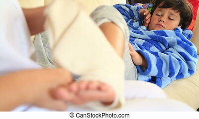 Nurse bandaging little boy ankle - Doctornurse hands...