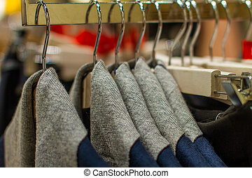 gray sweater hanging on a hanger in the store