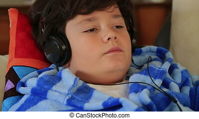 Young boy listening to music on a c - Happy child lying on a...