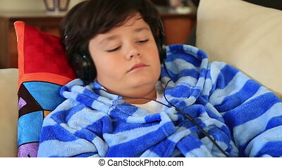 Young boy listening to music - Happy child lying on a sofa...