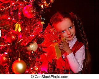 Child with gift box near Christmas tree. - Child with gift...