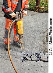 Asphalt demolishing, worker and jackhammer - Worker at...