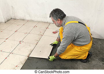 Home renovation, worker placing tiles to floor, using cement...