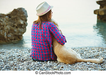 Woman with a dog sitting on the beach