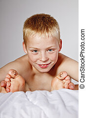 Boy in bed with smiley faces on his toes