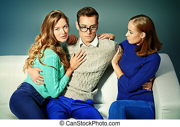 lovelace - Handsome young man sitting on the couch with two...