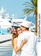 Attractive young couple walking alongside the marina with...