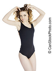 Sexy young woman posing in a black swimsuit isolated studio...