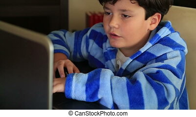 Young boy using computer - Cute schoolboy sitting at his...