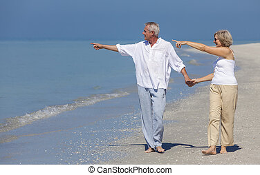 Happy Senior Couple Walking Pointing Holding Hands Beach