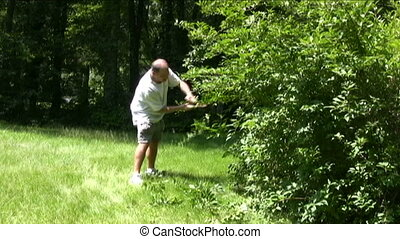 man trimming bushes with hand shears suburban homeowner