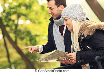 Young couple with map in the forest
