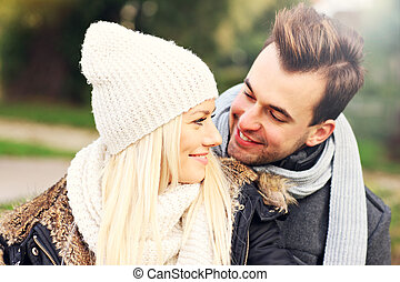 Young happy couple in the park in autumn