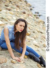 Young beautiful brunette girl sitting on the rocks on the...