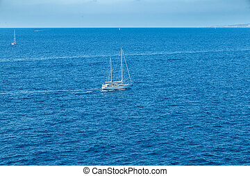 Sailing boats in open blue sea waters with clear blue sky