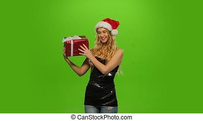 blond woman in Christmas cap with gift. green screen. Slow motion