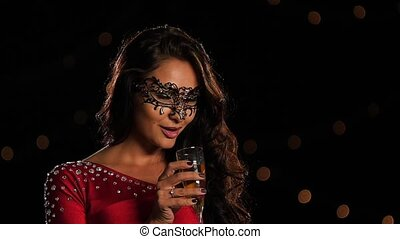 Beautiful woman in a carnival mask on dark. Slow motion