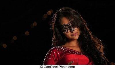 Beautiful brunette woman in a carnival mask on dark. Slow motion