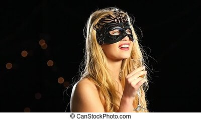 sexy blonde woman with venetian mask and glass of champagne...