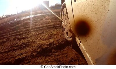 car auto goes through puddles and mud sun glare on water -...