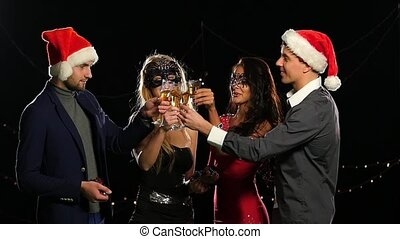 Boys and girls with flutes of champagne wishing you Merry Christmas. Slow motion. Close up
