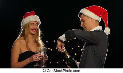Young happy couple opening champagne on New Year eve. Slow motion