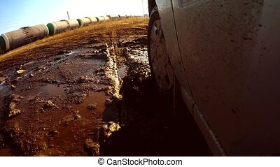 auto car through goes puddles and mud glare sun on water -...