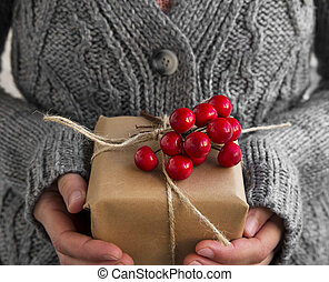 Holding Rustic Decorated Christmas Gift with Red Berries...