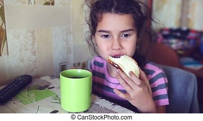 Teen girl eats bread with butter tea drinkers breakfast -...