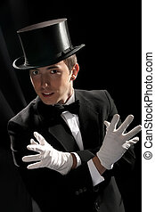 young magician with high hat on black background