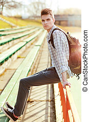 Fashion stylish young man with backpack in city