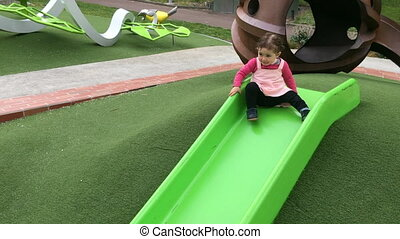 Little girl sliding on a slide in the playground