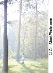 Lovely bride outdoors in a forest Sun rays beating down on...