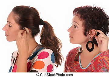 hearing aid - Two woman putting hearing aid into ear