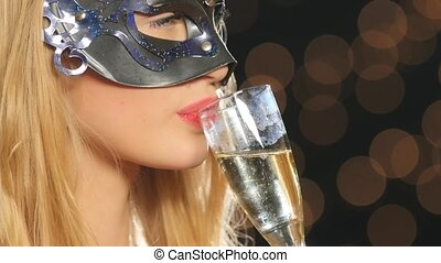 sexy blonde woman with venetian mask and glass of champagne, on black, bokeh