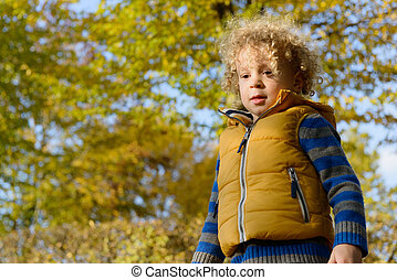 Closeup of little  cute boy with blonde curly hair, standing