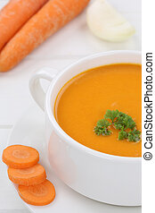Carrot soup with fresh carrots in bowl closeup