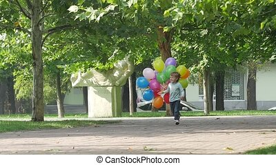 little girl runs with multicolored balloons, Slow motion