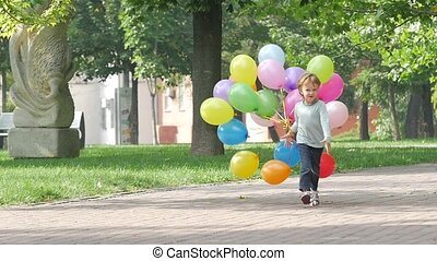 emotional little girl runs with multicolored balloons, Slow...