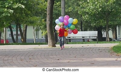 little girl runs with multicolored balloons, Summertime. Slow motion