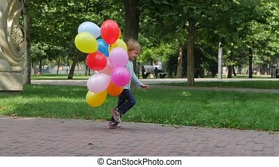 girl with multicolored balloons running into mother's hands to hug her. Slow motion