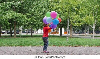 Little girl playing with multicolored balloons, Slow motion...