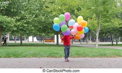 smiling girl playing with multicolored balloons, Slow motion...