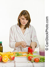 Young woman cuts sweet pepper vegetarian cooking Salad -...