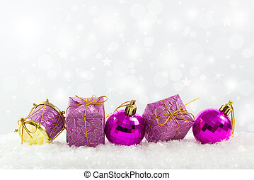 Purple Christmas ornaments in a row against defocused lights...