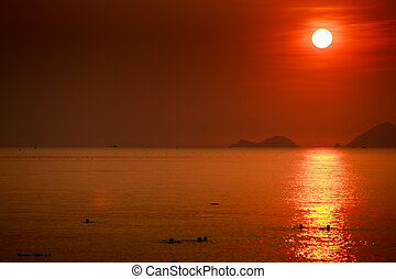 sun white disk among red sky above sea islands at sunrise -...
