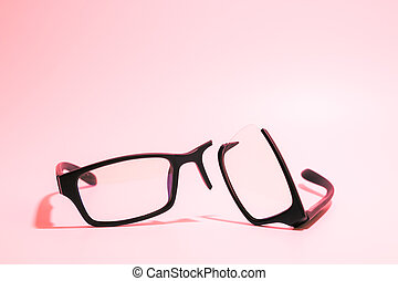 Closeup of Broken plastic Eyeglasses on colored background