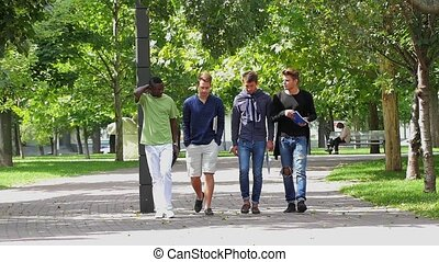 College men students walking together on campus. slow motion
